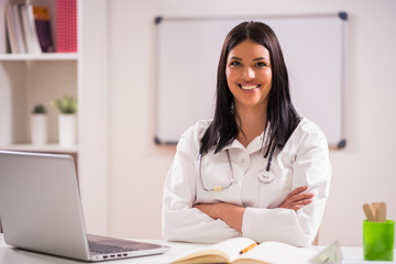 Portrait of young happy doctor in her office.