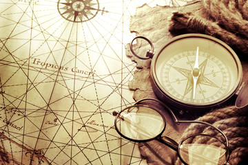 Vintage compass and glasses on antique map