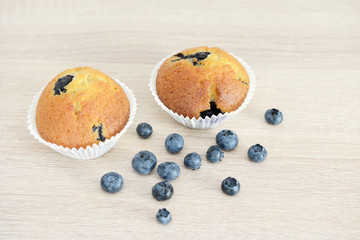 Muffin and blueberries on wood