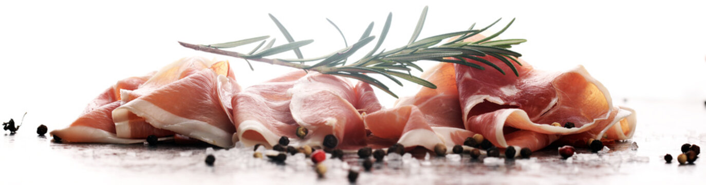 Italian prosciutto crudo or jamon with rosemary. Raw ham with spices