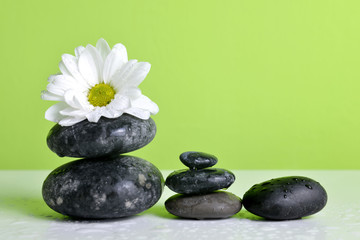 Zen pebbles and white flower on table. Spa and healthcare concept.