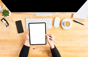 Female hands holding digital tablet and pencil. Top view of wooden office desk with tablet, pencil, large desktop computer, keyboard, mouse, smartphone and cup of coffee. Blank screen. Modern office.