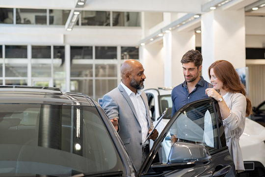 Couple examining new auto with car dealer