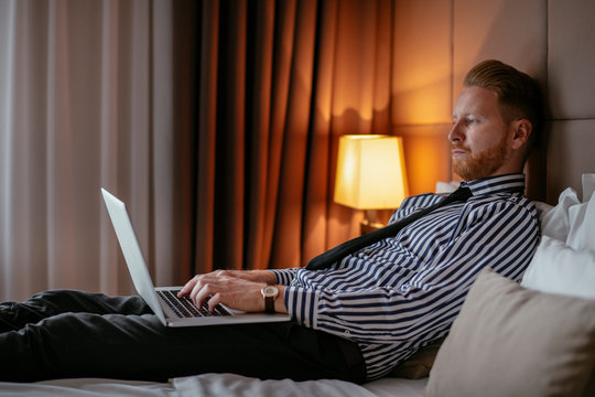 Manager takes a break, lays on the bed. Businessman relaxing in bed with a lap top beside him.