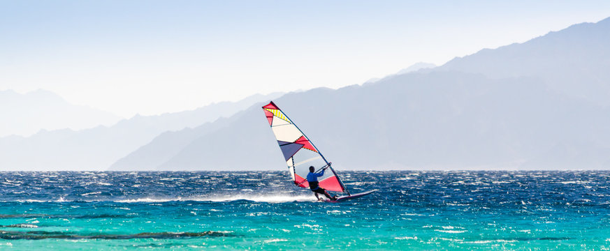 surfer rides in the Red Sea on the background of the rocky coast in Egypt Dahab