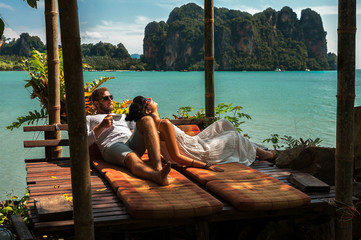 Loving couple resting in Asia. A young couple travels to exotic countries. Man and woman at the resort. Couple resting in Thailand. Honeymoon trip. Wedding travel. Man and woman on the Islands - fototapety na wymiar