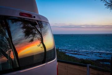 Reflection of tree silhouettes on camper van window in front of Indian Ocean in Australia Fototapete