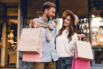 cheerful bearded man looking at woman in hat while holding shopping bags