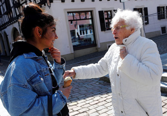 Lisel Heise, a 100-year-old former teacher, greets a teenager as she walks through Kirchheimbolanden