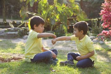 niños felices jugando a chocar los puños en el jardín al atardecer