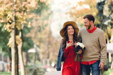 happy man looking at girlfriend in hat smiling while holding flowers