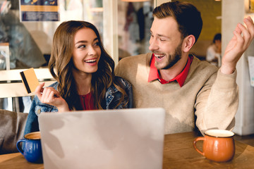 cheerful young woman holding credit card and looking at man near laptop