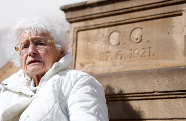 Lisel Heise, a 100-year-old former teacher, sits on a stone bench from 1921 in front of the townhall in Kirchheimbolanden