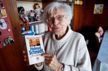 Lisel Heise, a 100-year-old former teacher, holds a book about former German Chancellor Helmut Schmidt as she meets journalists in the living room of her house in Kirchheimbolanden