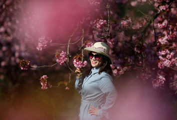 A tourist from Vietnam poses for a friend in front of pink cherry tree blossoms during a sunny spring morning at the Parc de Sceaux gardens