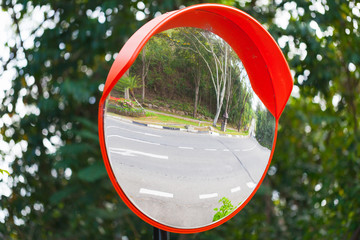 Round mirror in red frame on metal pole