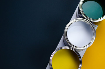Three cans of multicolored paint on a gray-orange with a white background.