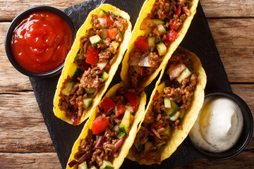 Authentic tacos with minced beef, cheese and vegetables are served with sauces close-up. horizontal top view