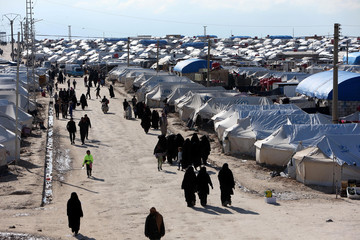 Women walk at al-Hol displacement camp in Hasaka governorate