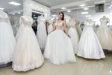 Bride in wedding dress fitting it in atelier