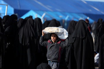 A boy carries bread on his head at al-Hol displacement camp in Hasaka governorate