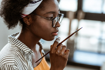 Close up of young talented artist holding little painting brush