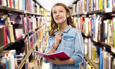 education, school, inspiration and people concept - teenage student girl in denim jacket with diary or notebook and pencil thinking over library background