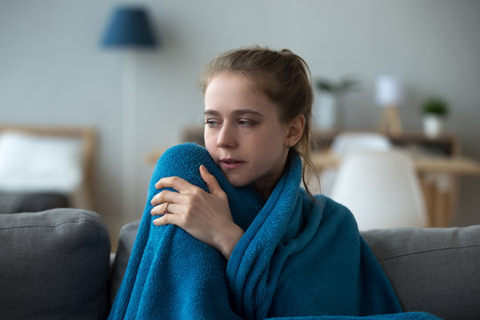 Upset sick woman covered with warm blue blanket, sitting on sofa