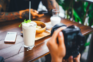 beautiful female photographs her food on camera. foodblogger