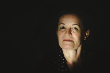 Portrait of a serene mature woman on dark background