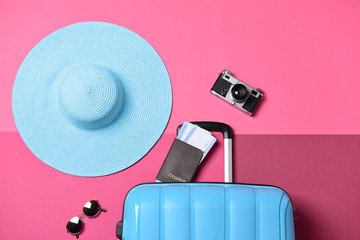 Suitcase, hat, photo camera and documents on color background. Travel concept