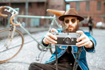 Bearded hipster dressed stylishly with hat and jacket sitting with photo camera and retro bicycle on the street outdoors