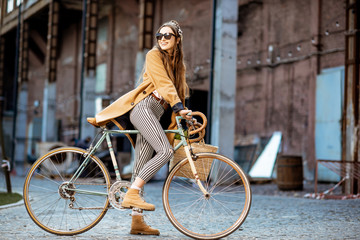 Full body portrait of a beautiful stylish woman dressed in coat standing with retro bicycle outdoors on the industrial urban background Fototapete