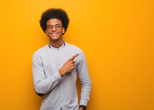 Young african american man over an orange wall smiling and pointing to the side