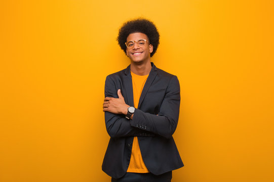 Young business african american man over an orange wall crossing arms, smiling and relaxed