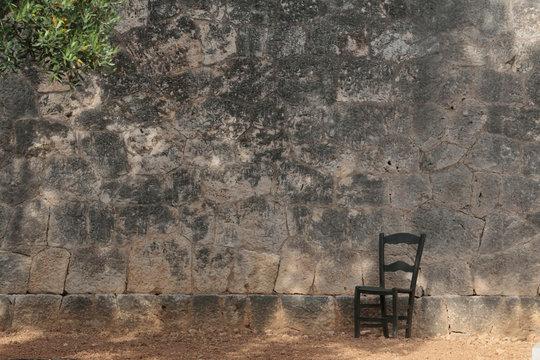Chair next to a memorial wall for Spanish civil war, Majorca, Spain