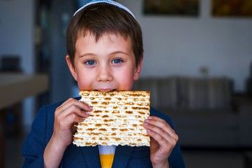Cute Caucasian Jewish boy holding in his hands and taking a bite from a traditional Jewish matzo unleavened bread. Jewish Passover Pesach concept image.