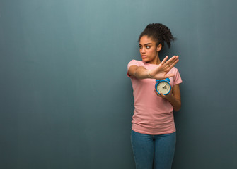 Young black woman putting hand in front. She is holding an alarm clock.