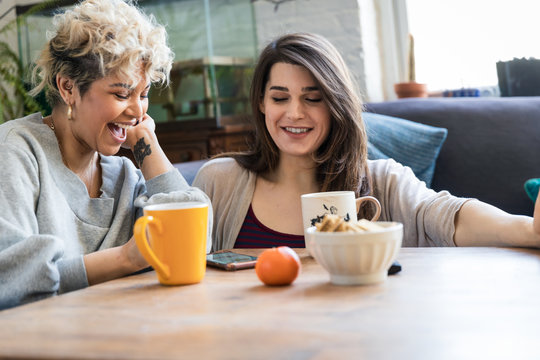 Two friends looking at a phone together at home