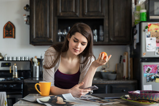 Transgender woman looking at her phone in the kitchen