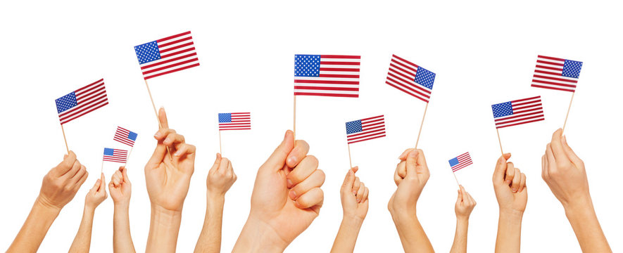 Hands holding and raising small flags of America