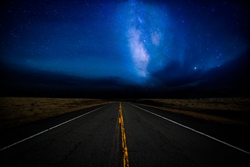 A highway disappearing into the distance illuminated by a star filled dramatic night sky in a rural landscape