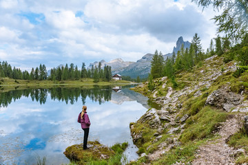 Sporty woman relaxing near by beautiful lake Federa in Dolomites Alps Italy