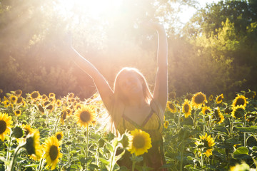 Beauty sunlit woman on yellow sunflower field Freedom and happiness concept. Happy woman outdoors