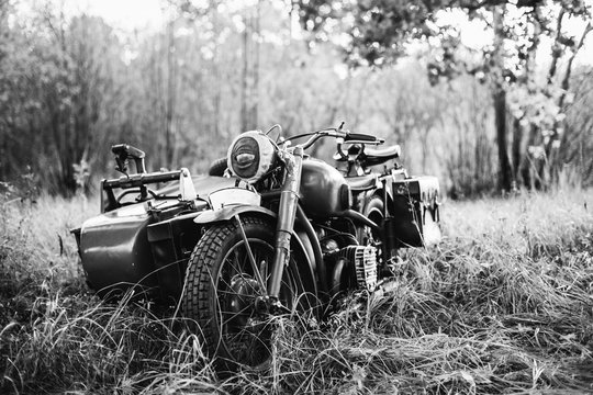 Old Tricar, Three-Wheeled Motorbike Of Wehrmacht, Armed Forces Of Germany Of World War II Time In Summer Forest. Photo In Black And White Colors