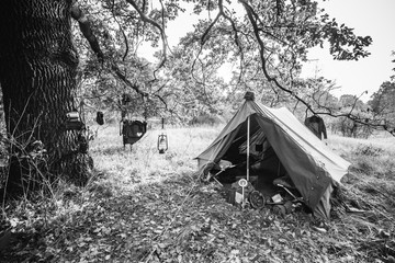 World War II German Wehrmacht Infantry Tent In Forest Camp. WWII WW2 German Ammunition. Photo In Black And White Colors