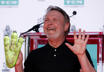 Actor Billy Crystal shows his hands after placing them in cement at the TCL Chinese Theatre in Hollywood