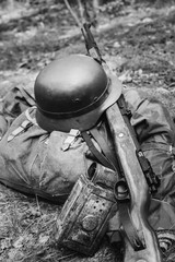 World War II German Wehrmacht Soldier Ammunition Of World War II On Ground.  WWII Military Helmet, Lights, Rifle Mauser Karabiner 98K. Photo In Black And White Colors
