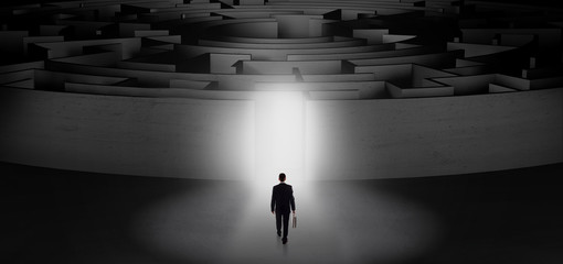 Wall Mural - Businessman getting ready to enter a concentric labyrinth with lighted entrance concept