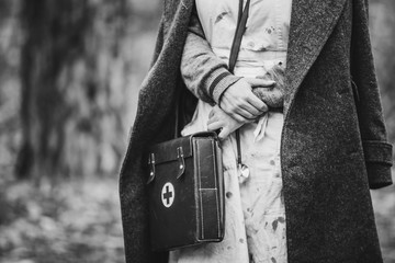Re-enactor Wears Historical German Nurse Paramedic Of World War II Uniform With First Aid Kit. Photo In Black And White Colors. WWII WW2
